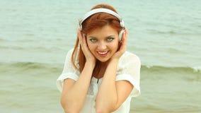 海滩的妇女听到音乐的 免版税库存照片