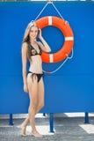 海滩的妇女在救生员塔附近和lifebuoy 免版税库存照片