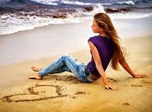 海滩的妇女在日落在沙子的文字爱 免版税库存照片