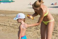 海滩的妈妈在遮光剂让一个小女孩回到 库存图片