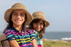 海滩的姐妹与帽子 免版税库存照片