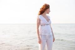 海滩的孕妇与在地中海的白光 免版税库存图片