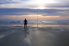 海滩的孤独的渔夫在微明 免版税库存照片