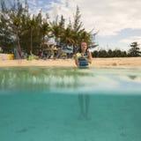 海滩的小女孩,半水下的看法 免版税库存图片