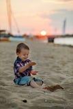 海滩的小男孩,使用与在日落的沙子 免版税图库摄影