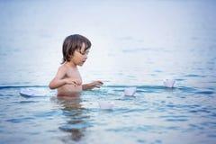 海滩的小逗人喜爱的男孩与纸小船 愉快的孩子pl 库存照片