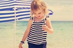 海滩的小滑稽的美丽的女孩 免版税库存照片