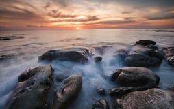 海滩的岩石波浪和日落 免版税库存图片
