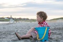 海滩的微笑的男孩与在日落的蓝色桶 库存图片
