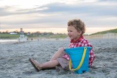 海滩的微笑的男孩与在日落的蓝色桶 免版税库存图片