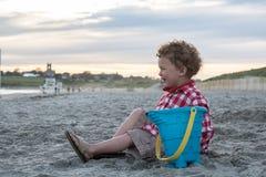 海滩的微笑的男孩与在日落的蓝色桶 库存照片