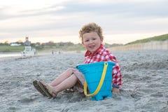 海滩的微笑的男孩与在日落的蓝色桶 图库摄影