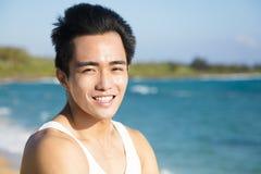 海滩的微笑的年轻人 免版税库存图片