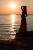 海滩的怀孕的女孩在海滩的日落 免版税库存图片