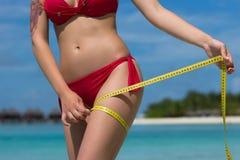 海滩的性感的妇女在有措施磁带的比基尼泳装 作为背景诱饵概念美元灰色吊异常分支 免版税库存图片