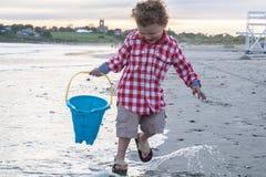 海滩的愉快的小男孩与在日落的蓝色桶 库存图片
