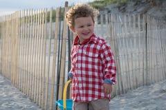 海滩的愉快的小男孩与在日落的蓝色桶 免版税库存图片