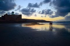 海滩的朋友在日落 免版税库存照片