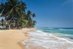 海滩的未认出的人在Hikkaduwa Hikkaduwa的海滩和夜生活做它一个普遍的旅游目的地 免版税库存图片