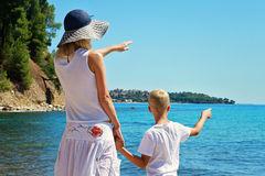 海滩的母亲和儿子 在海前面的妇女和男孩儿子,指向去,活跃暑假假期,家庭旅行照片 库存图片