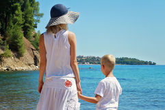 海滩的母亲和儿子 在海,活跃暑假假期,家庭旅行照片前面的妇女和男孩儿子 免版税库存图片