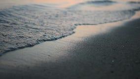 海滩的涅磐-金黄日落的平安的田园诗场面在海的,慢慢地飞溅在沙子的波浪 股票录像