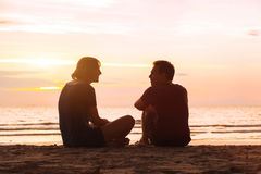 海滩的男人和妇女在日落 库存照片