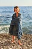 海滩的男孩穿爸爸` s夹克 免版税库存图片
