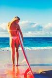 海滩的白肤金发的冲浪者女孩 库存照片