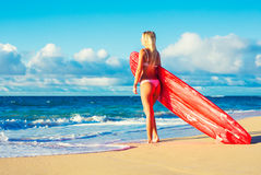 海滩的白肤金发的冲浪者女孩 库存图片