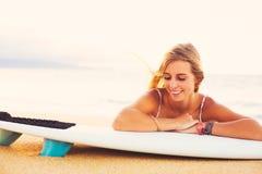 海滩的白肤金发的冲浪者女孩 免版税库存图片
