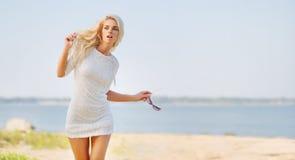 海滩的白肤金发的美丽的妇女 免版税图库摄影