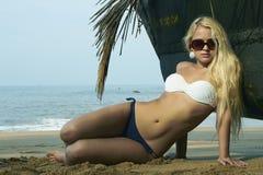 海滩的秀丽白肤金发的妇女在小船附近 免版税库存图片