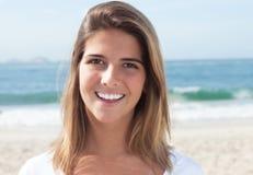 海滩的笑的白肤金发的妇女 免版税库存照片
