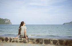 海滨的美丽的单独年轻亚裔妇女在海滩附近 被弄脏的海和天空在背景中 选择聚焦 被过滤的图象 免版税库存图片