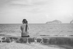 海滨的美丽的单独年轻亚裔妇女在海滩附近 被弄脏的海和天空在背景中 选择聚焦 被过滤的图象 库存照片