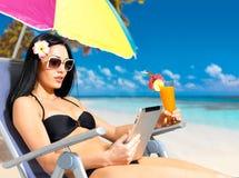 海滩的美丽的妇女与ipad 免版税库存照片