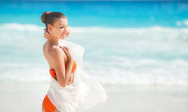 海滩的美丽的妇女在橙色比基尼泳装 免版税图库摄影