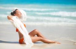 海滩的美丽的妇女在橙色比基尼泳装 库存照片