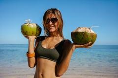 海滩的美丽的妇女用新鲜的椰子 图库摄影