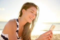 海滩的美丽的少妇与巧妙的电话 免版税库存照片