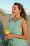 海滩的美丽的深色的妇女与一朵黄色玫瑰 免版税库存图片