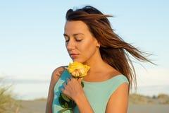 海滩的美丽的深色的妇女与一朵黄色玫瑰 免版税库存照片