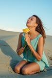 海滩的美丽的深色的妇女与一朵黄色玫瑰 库存图片