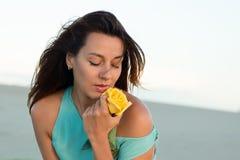 海滩的美丽的深色的妇女与一朵黄色玫瑰 免版税图库摄影