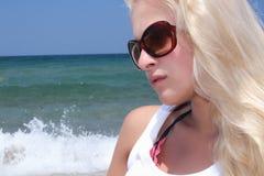 海滩的美丽的白肤金发的妇女在太阳镜 免版税库存图片