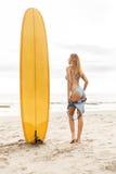 海滩的美丽的运动的冲浪者女孩 免版税库存图片