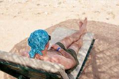 海滩的英俊的人睡觉在他的轻便折叠躺椅的 图库摄影