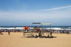 海滩的许多人民反对海洋和蓝色地平线 免版税库存图片