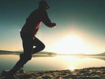 海滩的连续人 在棒球帽跑的运动员 免版税库存图片